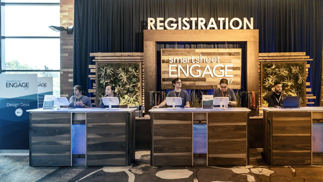 Volunteers work at the registration kiosk at the Smartsheet ENGAGE customer conference