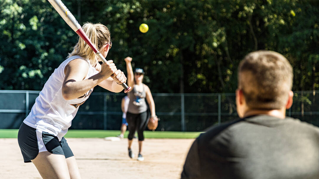 Men and women play underhand softball in a park.