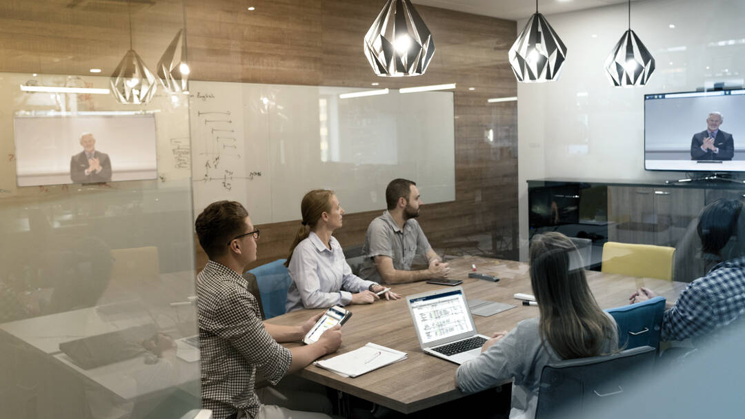 Employees participating in video teleconference