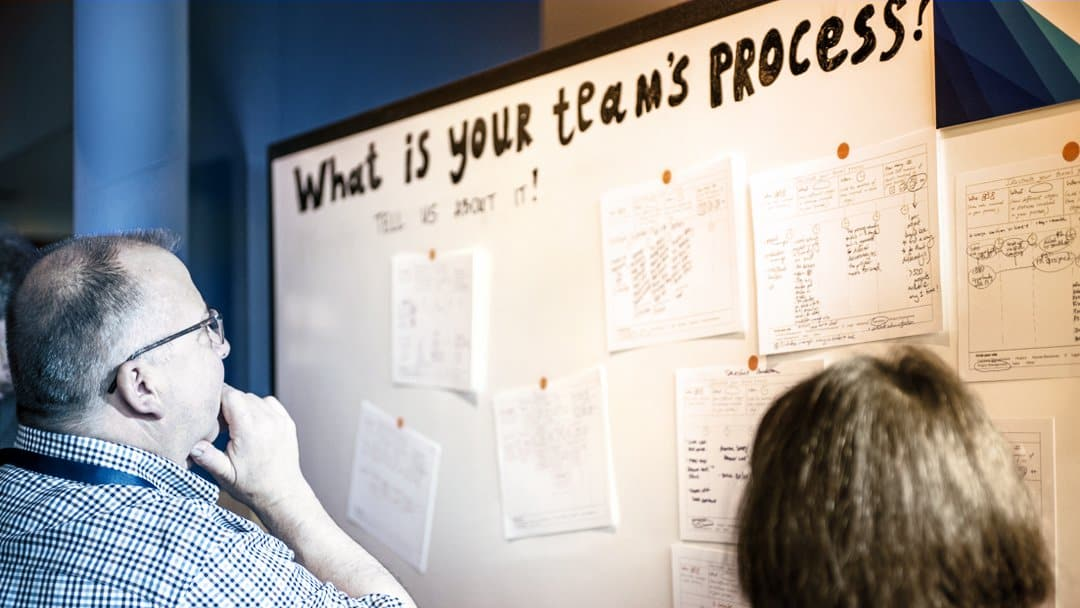 "A man looks at a whiteboard that reads ""What's your team's process?"""