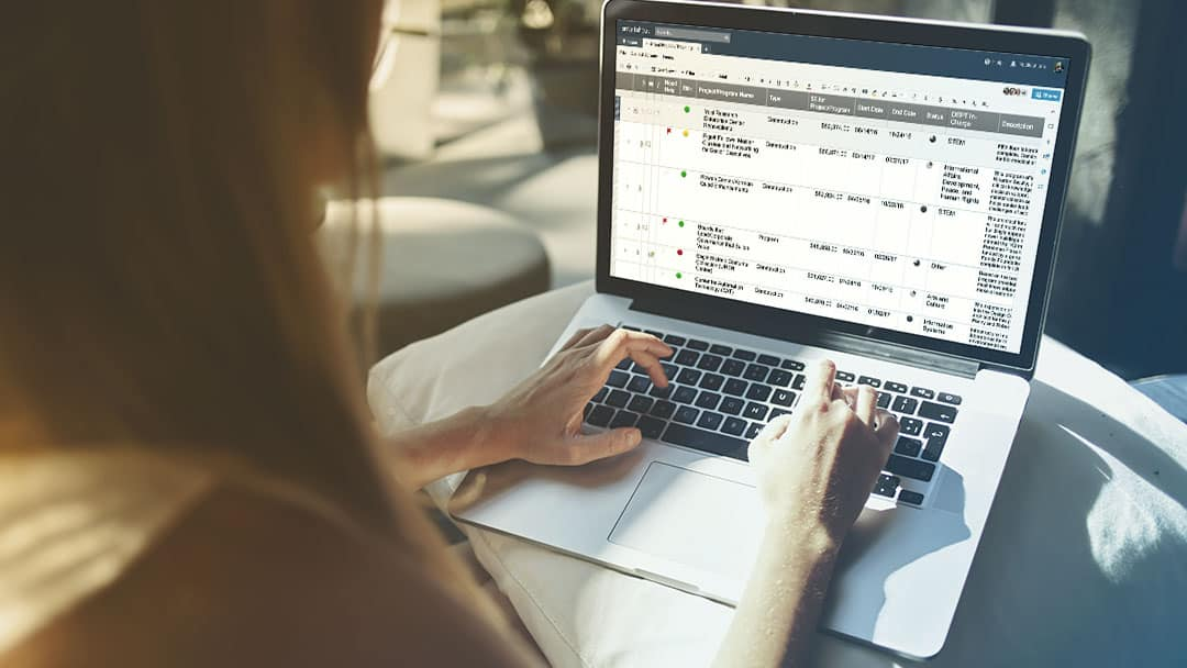 A business woman views Smartsheet in grid view on a laptop