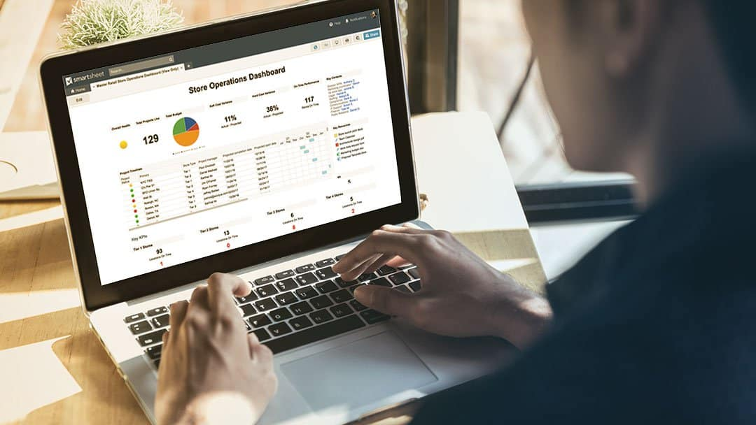 A man views a store operations dashboard on Smartsheet