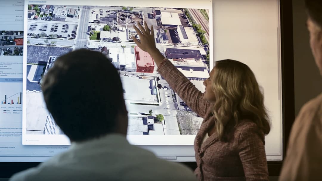 A woman gestures to an image of commercial real estate properties on a large monitor