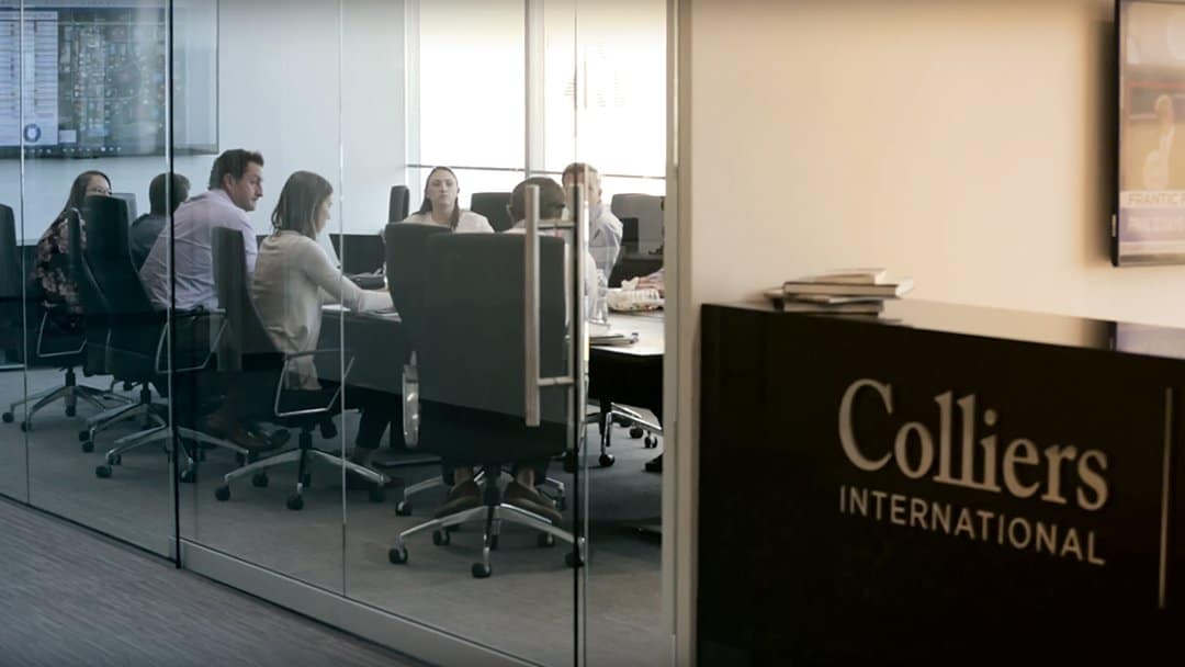 Colliers International employees meet in a conference room with glass walls and doors