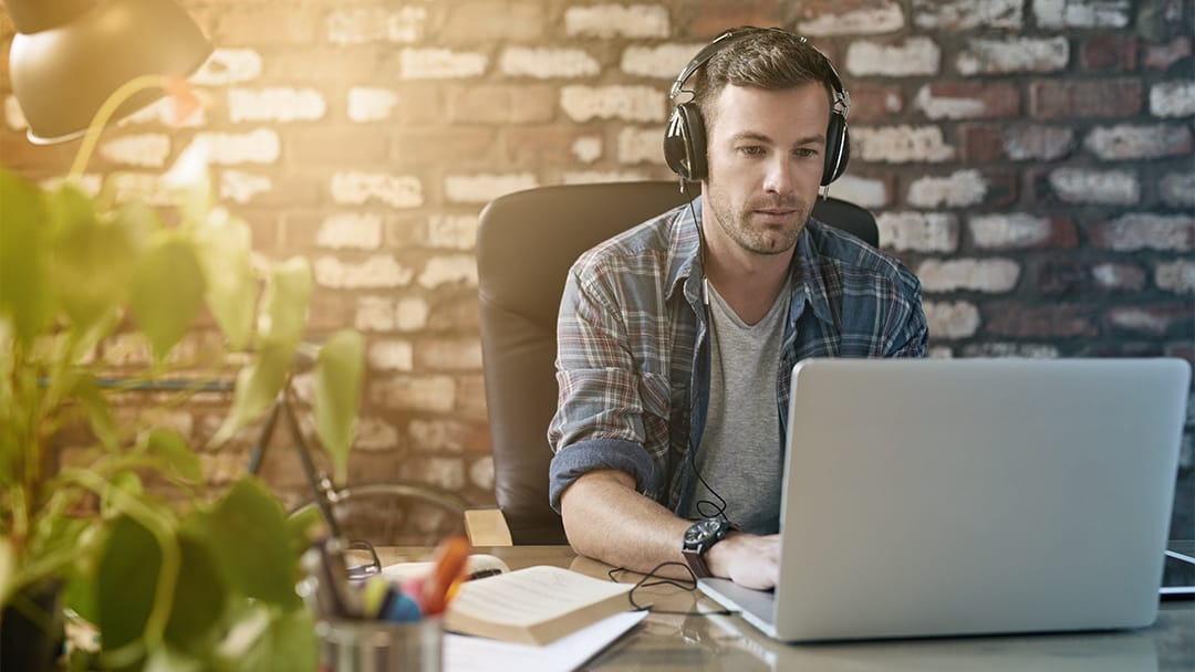 A male worker wears headphones and types on a laptop.