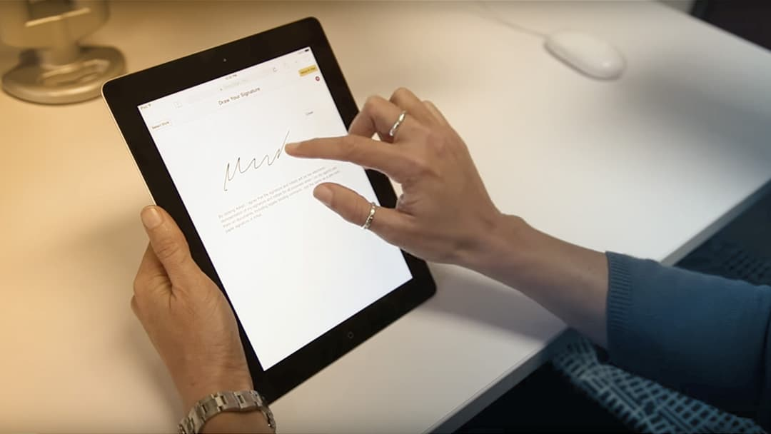 A woman signs a digital document on a tablet computer.