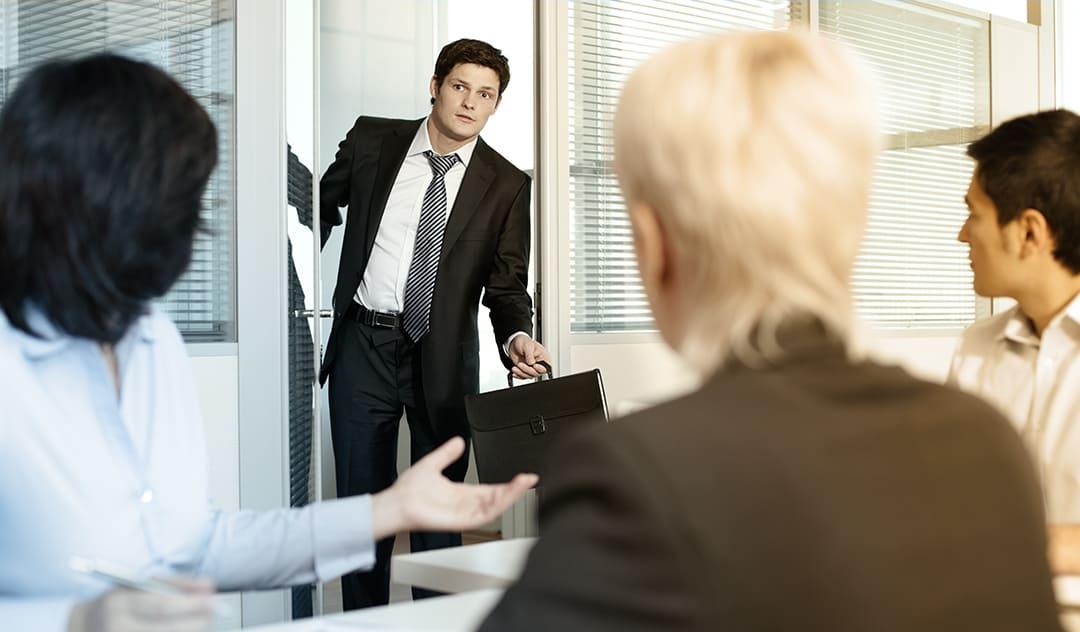 A young man interrupts a meeting.