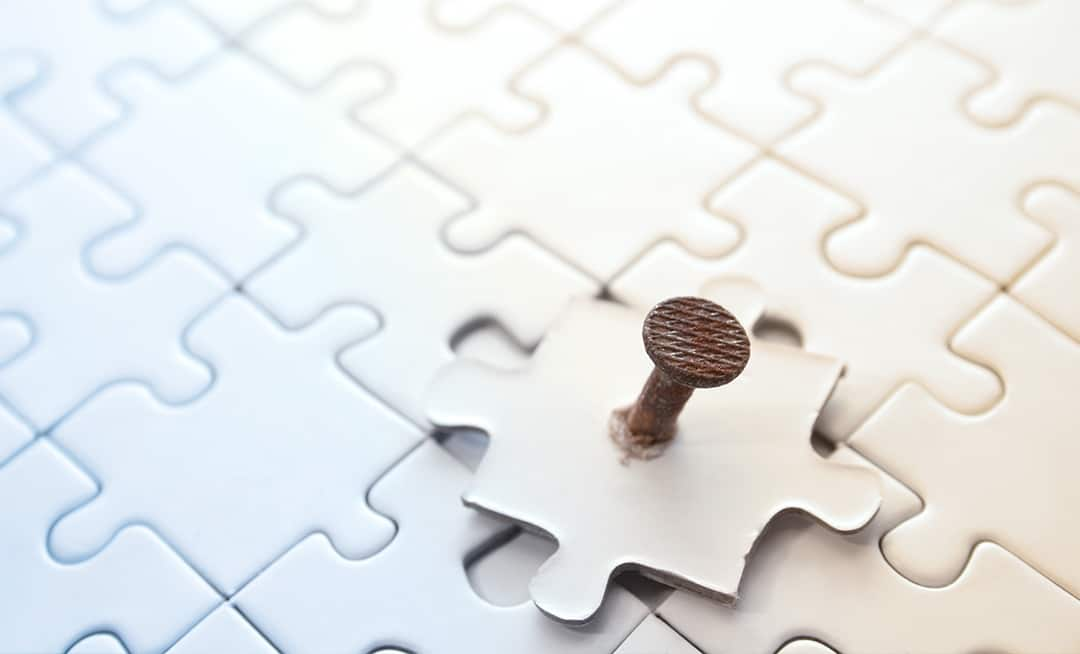 A rusty nail pierces a puzzle piece that is not correctly aligned.