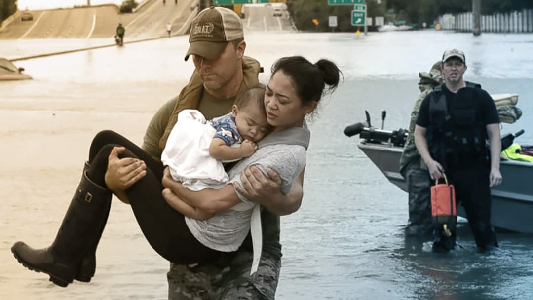 A man carries a woman and her baby above a flooded street.