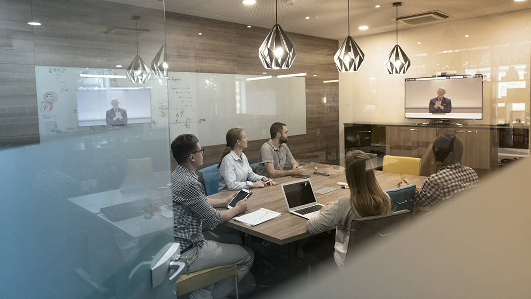 Workers at a conference table connect with a remote worker via video