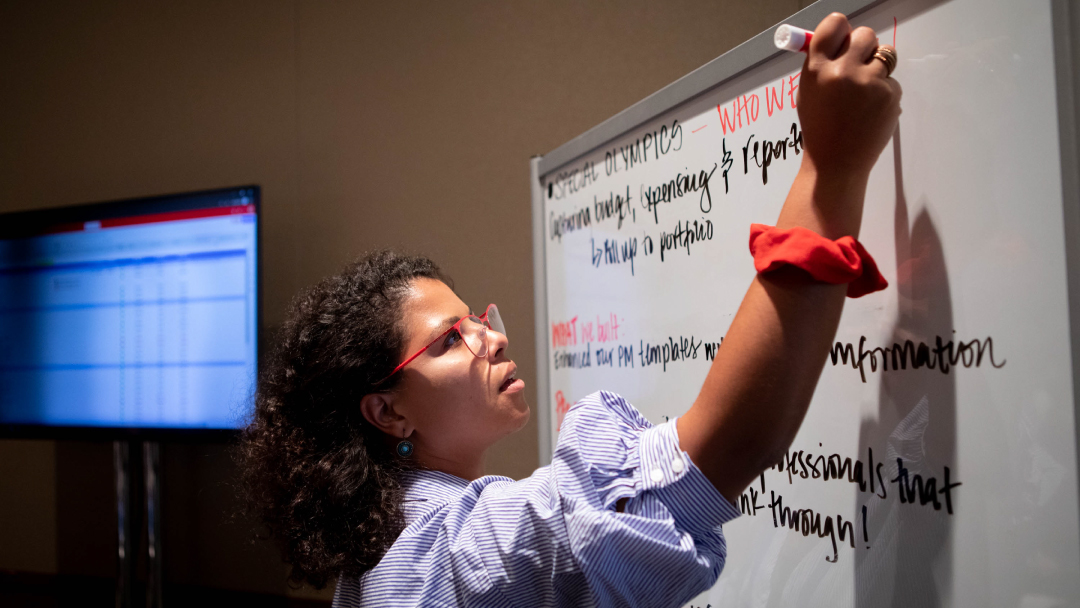 An image of a woman with curly hair pulled back, sleeves pushed up, writing on a whiteboard