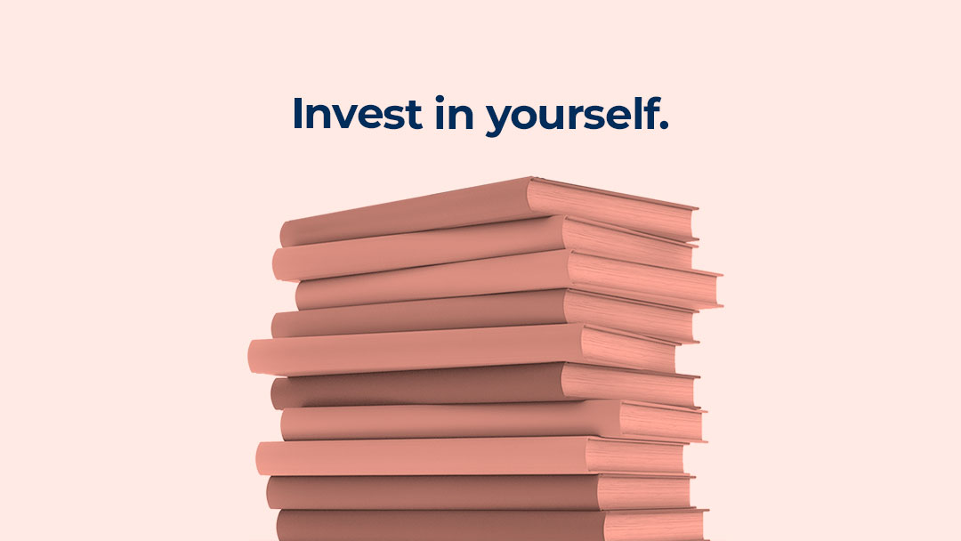 "A rosey-pink-hued stack of books appears on a pale blush pink background with the words ""Invest in yourself"" appearing in dark blue atop the bookstack"