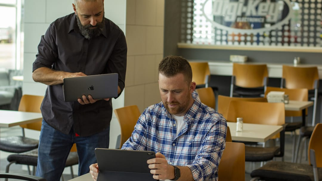 Employees work on a tablet and laptop in the Digi-Key cafeteria