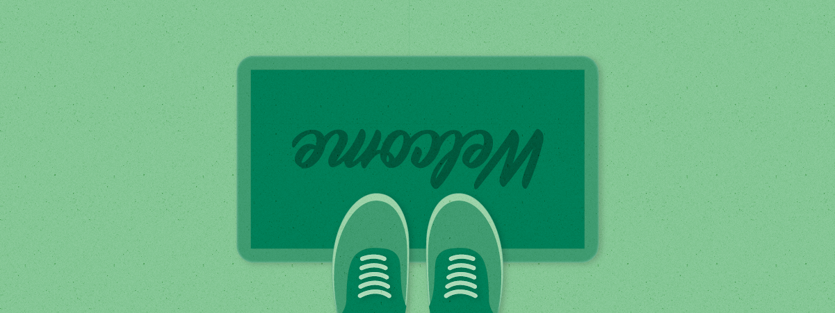 Two green shoe-covered feet appear on a doormat that says welcome upside down as though you're standing above it looking down