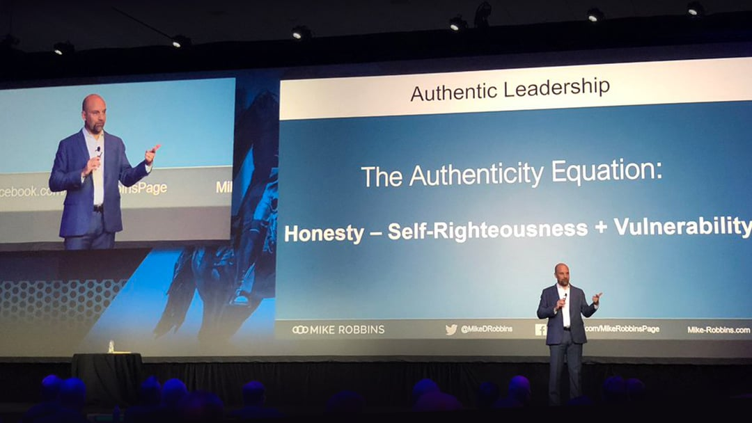 "Mike Robbins delivers a keynote at a corporate event, presentation slide reads: ""The Authenticity Equation: Honesty - Self-Righteousness + Vulnerability"""