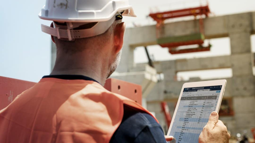 An on-site construction project manager uses Smartsheet on a tablet