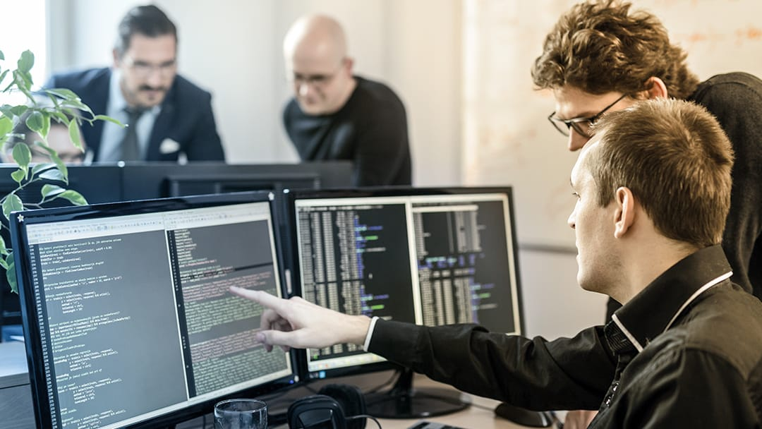 A technology worker points at the software code on a colleague's desktop computer screen.
