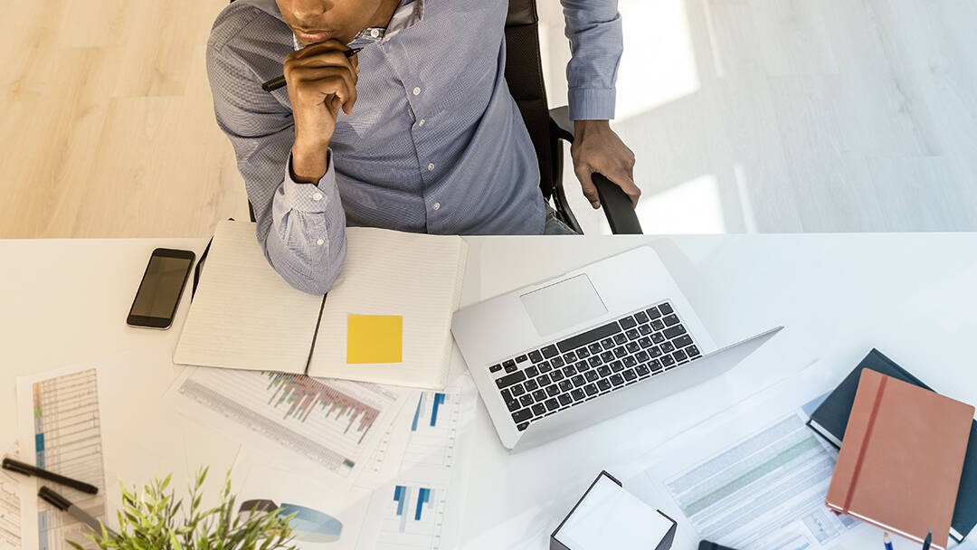 A businessman takes a moment to think before writing at his office desk.