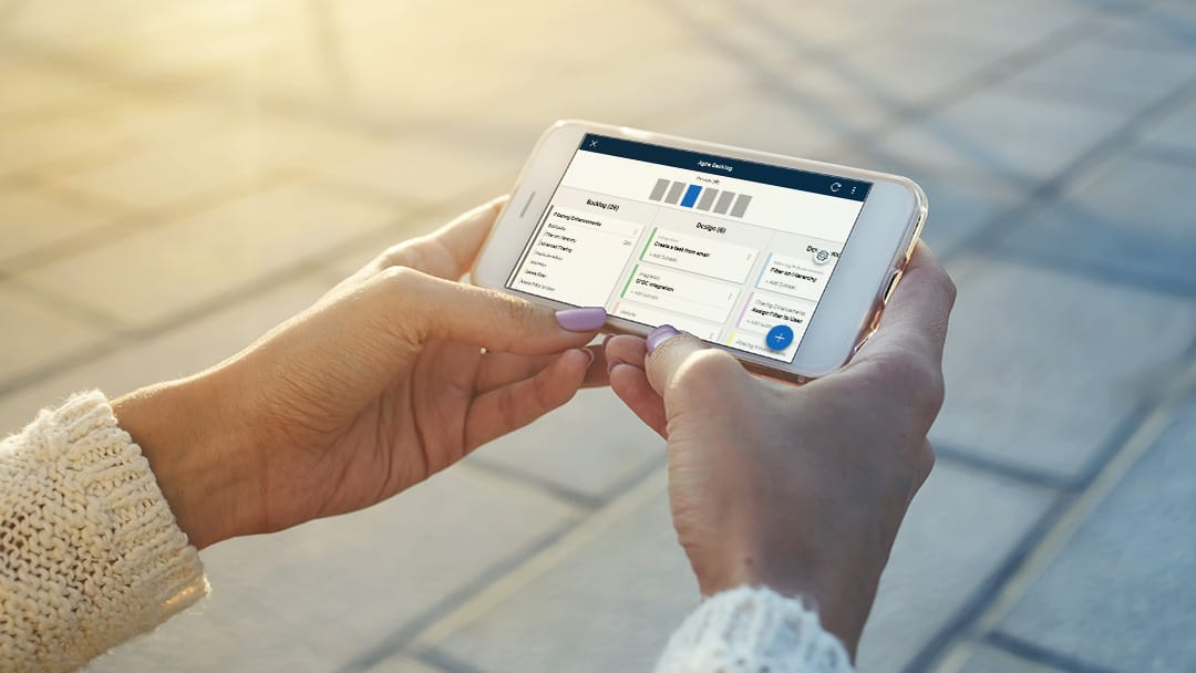 A woman views project tasks using Smartsheet card view on a smartphone